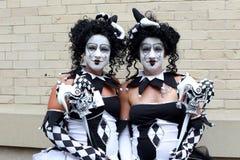Identiska unga kvinnor kopplar samman förklätt som harlekiner Royaltyfri Bild