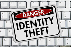 Identity Theft Danger Sign. A red and white sign with the words Identity Theft on a keyboard stock images