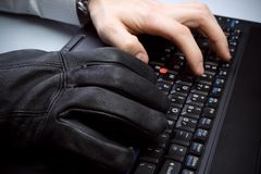 Identity theft with hands on laptop computer. Identity theft, security concept with businessman and hacker hands on laptop keyboard stock photography