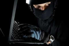 Identity theft with man working on laptop. Identity theft. Security concept with sneaky thief stealing computer data from laptop at night stock image