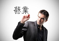 Ideograms. Elegant young man writing some chinese ideograms Royalty Free Stock Photography