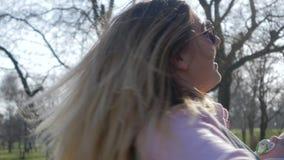 Idilio de la familia, mamá feliz con el niño en honda y pelo del vuelo en la naturaleza en vacaciones metrajes