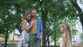 Idilio de la familia, mamá feliz con gafas con el padre que mira a la muchacha del niño y que abraza aire libre almacen de metraje de vídeo