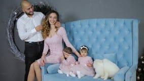 Idilio de la familia, pareja feliz con los niños que presentan en la sesión de foto con dos perritos en el sofá azul almacen de video