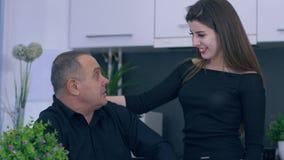 Idilio, papá e hija de la familia hablando y abrazándose durante el desayuno en cocina almacen de metraje de vídeo
