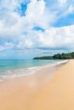 Idillic sand beach with calm blue sea. Idyllic sand beach with calm blue sea coast, cloudy sky and green tree hills on background Stock Photos
