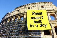 Idiom Rome wasn't built in a day postit Colosseum. Idiom Rome wasn't built in a day on large postit affixed on Colosseum in Rome Stock Images