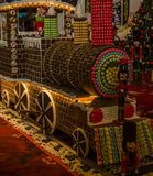 Merry Christmas and happy New Year!. The idiosyncratic Christmas tree and candy            Locomotive  is placed in the Plaza of the building Royalty Free Stock Images
