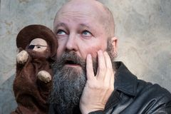 Idiosyncratic crazy artist Father with beard, with astonished expression, plays with a hand puppet. Idiosyncratic crazy artist Father with beard, with astonished royalty free stock image
