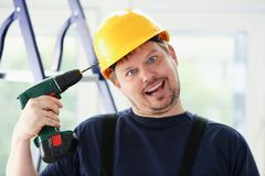 Idiot worker using electric drill portrait. Manual job, DIY inspiration, improvement, fix shop, yellow helmet, joinery startup idea, industrial education Royalty Free Stock Photos