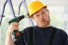 Idiot worker using electric drill portrait Royalty Free Stock Images