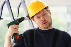 Idiot worker using electric drill portrait. Manual job, DIY inspiration, improvement, fix shop, yellow helmet, joinery startup idea, industrial education Royalty Free Stock Image
