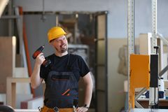 Idiot worker using electric drill portrait. Manual job DIY inspiration improvement fix shop yellow helmet joinery startup idea industrial education profession Stock Image
