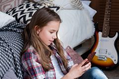 Idle child leisure girl using mobile phone home. Idle child leisure. girl using mobile phone at home. internet browsing and social network chatting stock photography
