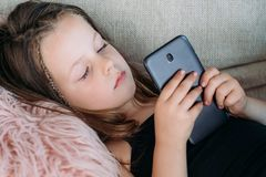 Idle child leisure girl browsing mobile phone. Idle child leisure. little girl browsing internet or watching videos on mobile phone. modern technology invasion royalty free stock images