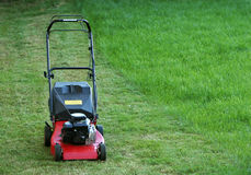 Idle lawnmower. Standing on green grass, partly mowed but part still left to mow Stock Photography