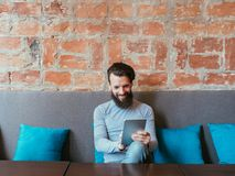 Idle leisure internet addiction tablet apps gaming. Idle leisure and internet addiction. man smiling while using tablet. apps and gaming stock photography