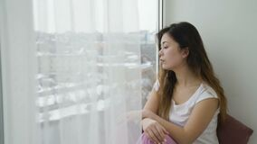 Idle leisure relaxed calm teen girl sitting window. Idle leisure. relaxed calm teen girl sitting on the windowsill and looking out of the window stock footage