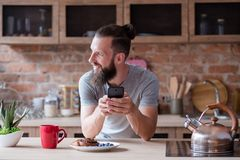 Idle leisure addiction man phone kitchen breakfast. Idle lifestyle and leisure. internet and social network addiction. man using phone during breakfast at home royalty free stock photography