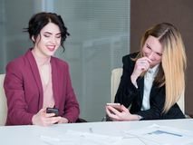 Idle worker mobile phone laugh business women. Idle workers looking at their mobile phones laughing. irresponsible lazy business women at work royalty free stock images