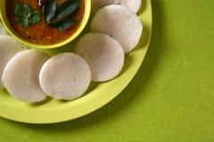 Idli med sambaren i bunke på grön bakgrund, indisk maträtt arkivfoto