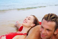 Idling. A portrait of attractive couple having fun on the beach. Focused on girl's face royalty free stock photos