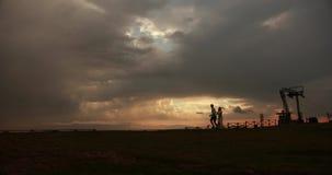 Ido com o vento Imagem de um par bonito que corre ao longo da estrada no monte com por do sol vermelho e cinzento bonito vídeos de arquivo