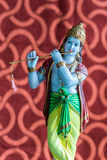 Idol of Lord Krishna. Lord Krishna with his favorite musical instrument, the flute, in this idol Stock Photo