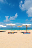 Idollic beach relaxing concept with white parasols on sand Stock Photos