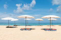 Idollic beach relaxing concept with white parasols on sand Royalty Free Stock Photo