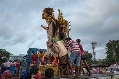 Idolo di Durga che è portato giù da un camion dal gruppo di lavoratori per l'immersione nel Gange Fotografia Stock