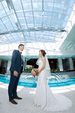 Idoors de jeunes mariés à la piscine Photo libre de droits