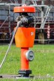 Idrante antincendio rosso con la manichetta antincendio Immagini Stock