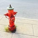 Idrante antincendio rosso sulla via urbana fotografia stock