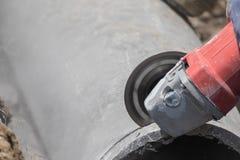 Idraulici che tagliano le tubature dell'acqua concrete Immagini Stock Libere da Diritti