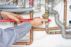 Idraulico che ripara il sistema del riscaldamento centrale Immagine Stock
