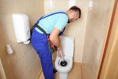 Idraulico che ripara toilette con il tuffatore della mano immagini stock