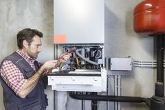 Idraulico che ripara una caldaia di condensazione fotografia stock