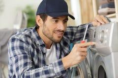 Idraulico felice che ripara lavatrice immagine stock libera da diritti