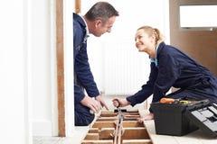 Idraulico And Female Apprentice che misura il sistema del riscaldamento centrale Fotografia Stock Libera da Diritti