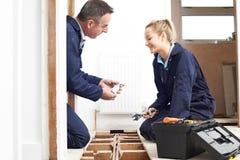 Idraulico And Female Apprentice che misura riscaldamento centrale Fotografia Stock