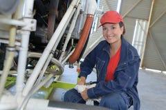 Idraulico femminile che lavora alla caldaia per il riscaldamento centralizzato della fabbrica fotografia stock libera da diritti