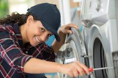 Idraulico femminile che ripara lavatrice fotografia stock