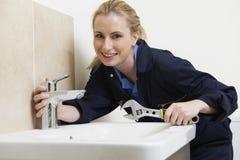 Idraulico femminile Working On Sink che per mezzo della chiave fotografia stock libera da diritti