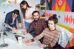 Idérikt lag av fyra kollegor som arbetar i modernt kontor Arkivbilder