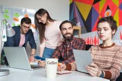 Idérikt lag av fyra kollegor som arbetar i modernt kontor Royaltyfri Fotografi