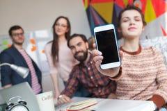 Idérikt lag av fyra kollegor som arbetar i modernt kontor Arkivfoton