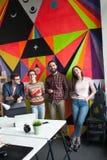 Idérikt lag av fyra kollegor som arbetar i modernt kontor Royaltyfri Bild