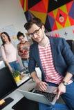 Idérikt lag av fyra kollegor som arbetar i modernt kontor Royaltyfri Foto