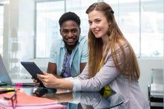 Idérikt ungt affärsfolk som ser den digitala minnestavlan Royaltyfria Foton